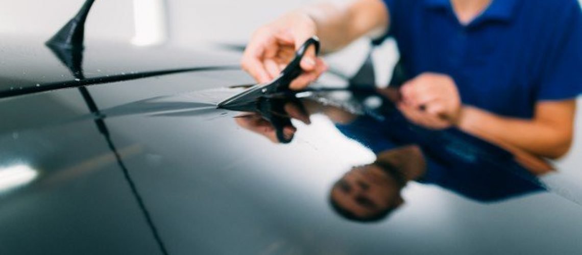 male-worker-with-scissors-car-tinting-film-installation-process-tinted-auto-glass-installing-procedure_266732-11595